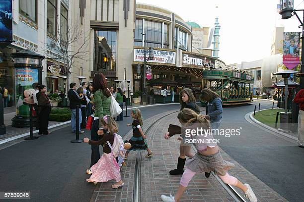 3/4 TO GO WITH AFP STORY USSOCIETYDISTRIBUTIONREAL ESTATE Shoppers cross a street lined at The Grove outdoor shopping mall 24 April in Los Angeles...