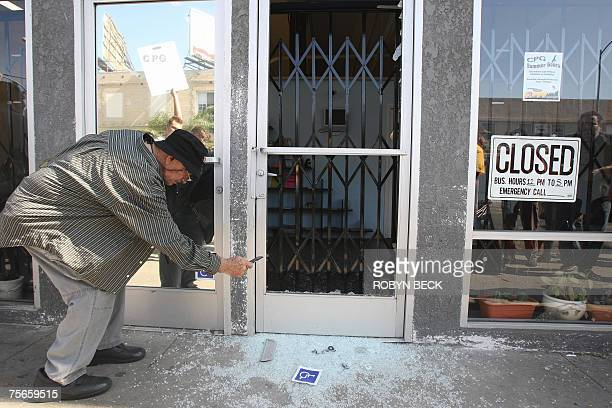 A medical marijuana advocate uses his cell phone to photograph the front door of a medical marijuana dispensary which was broken during a raid by...
