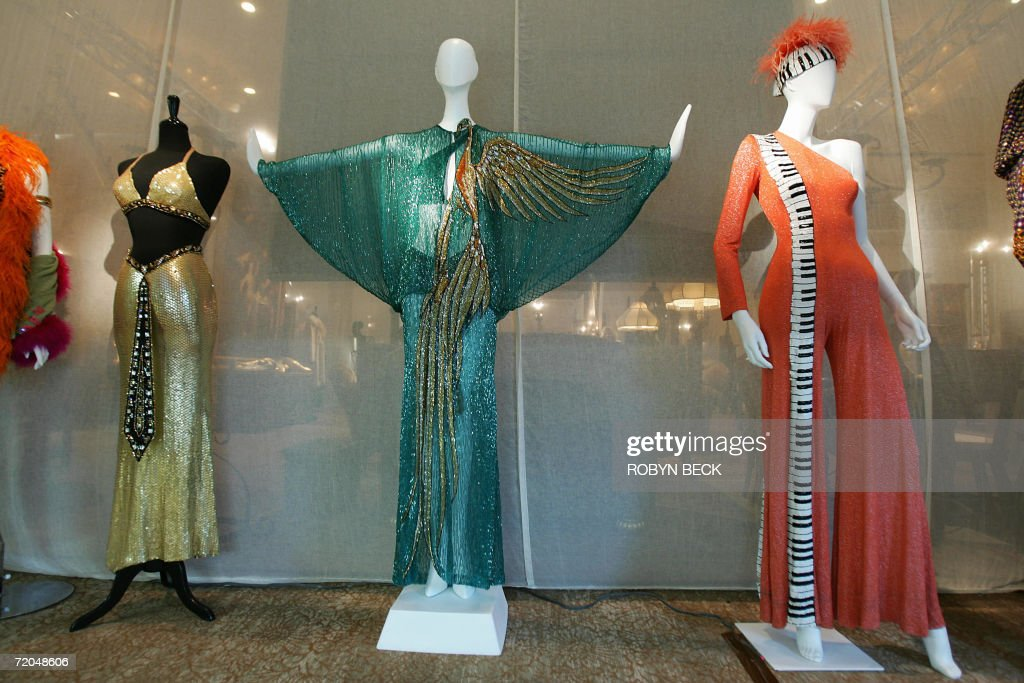 A phoenix dress (C) and a keyboard motif jumpsuit (R), both designed by Bob Mackie for Cher, are on view at a public auction preview 29 September 2006 in Los Angeles. Sotheby's will auction off furniture, clothing, jewelry, art, books and more from Cher's 16,000-square-foot (1,486 sq.-meter) Malibu Italian Renaissance mansion on 03-04 October in Los Angeles. Cher told the Los Angeles Times that she is selling off much of the contents of the home so you she can redecorate in Tibetan, Moroccan, Indian and Zen style. AFP PHOTO/Robyn BECK