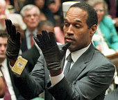 This 21 June 1995 file photo shows former US football player and actor OJ Simpson looking at a new pair of Aris extralarge gloves that prosecutors...
