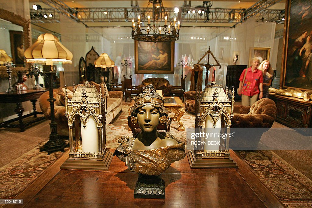 Two visitors walk through a room of furnishing from the Malibu home of Cher, including in the foreground an art nouveau bronze bust by Emmanuel Villanis (circa 1900) during a public auction preview 29 September 2006 in a Los Angeles hotel. Sotheby's will auction off furniture, clothing, jewelry, art, books and more from Cher's 16,000-square-foot Malibu Italian Renaissance mansion on 03-04 October in Los Angeles. Cher told the Los Angeles Times that she is selling off much of the contents of the home so you she can redecorate in Tibetan, Moroccan, Indian and Zen style. AFP PHOTO / Robyn BECK