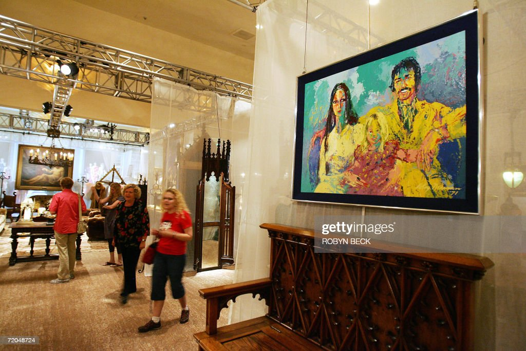 Two visitors walk through a room of furnishing from the Malibu home of Cher, including in the foreground a Leroy Neiman portrait of Sonny, Cher and Chastity Bono during a public auction preview 29 September 2006 in a Los Angeles hotel. Sotheby's will auction off furniture, clothing, jewelry, art, books and more from Cher's 16,000-square-foot Malibu Italian Renaissance mansion on 03-04 October in Los Angeles. Cher told the Los Angeles Times that she is selling off much of the contents of the home so you she can redecorate in Tibetan, Moroccan, Indian and Zen style. AFP PHOTO / Robyn BECK