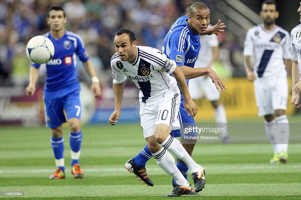 los10 heads the ball in front of Matteo Ferrari of the Montreal Impact during the MLS match at the Olympic Stadium on May 12 2012 in Montreal Quebec...