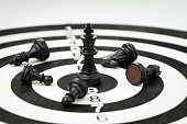 Lose some to win some metaphor in business success strategy or leadership concept, black winner chess king at the center of dartboard surrounded by injure or died knight, crisis management.