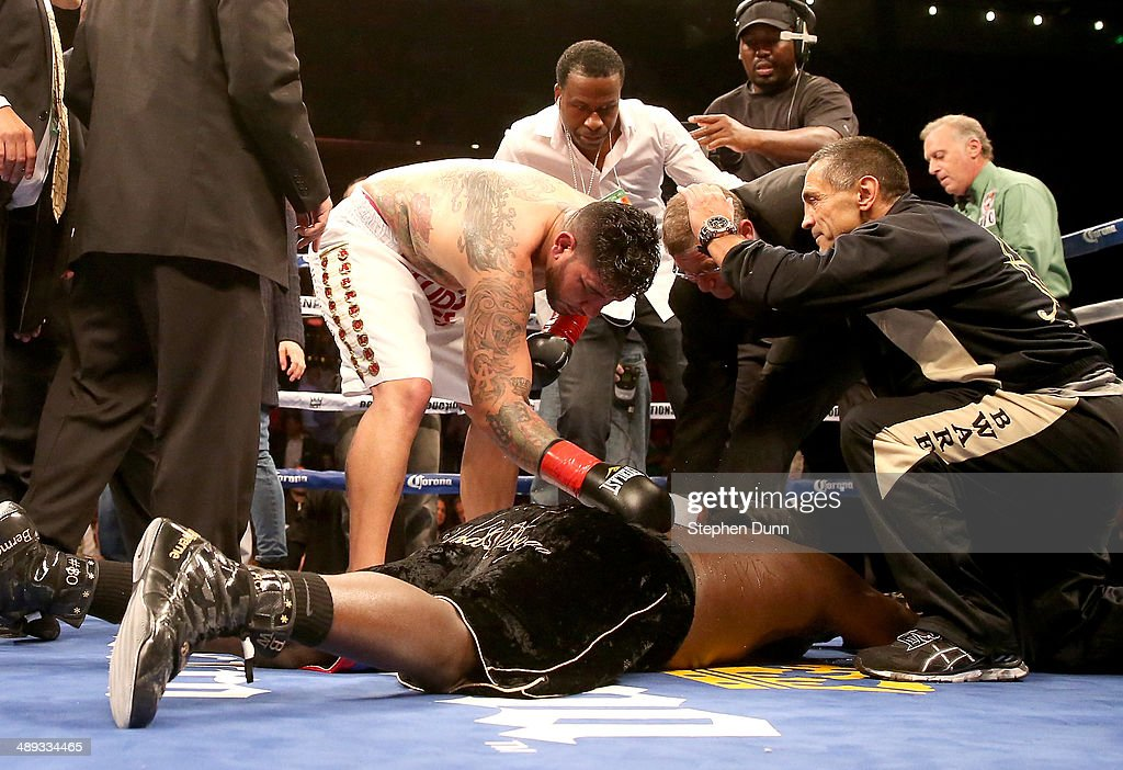 Loser Chris Arreola leans over winner Bermane Stiverne, who fell to the canvas in celebration after their WBC Heavyweight Championship match at Galen Center on May 10, 2014 in Los Angeles, California. Stiverne won in a six round technical knockout.