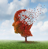 Brain disease with memory loss due to Dementia and Alzheimer's illness with the medical icon of an autumn season color tree in the shape of a human head and brain losing leaves as a concept of intelli