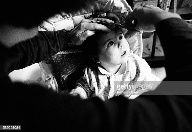 Losing the hair I was born with We look over the darkened shoulder of a mother as she cuts her baby daughter's hair at home for the first time...