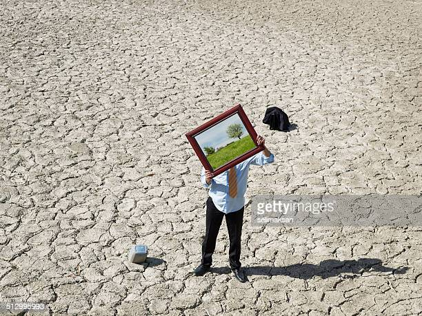 Lost businessman in desert showing picture frame with green view