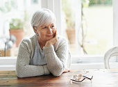 A senior woman sitting at her kitchen table lost in thought