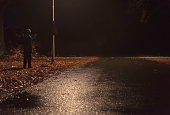 Lost man stands by the side of the road at night.