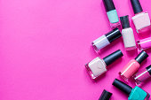 lot of bottles of nail polish on pink background top view