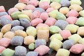 A lot of colorful candy. Close up macro, on wooden table.