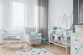 Shot of a bright child's room with white curtains and a classic armchair