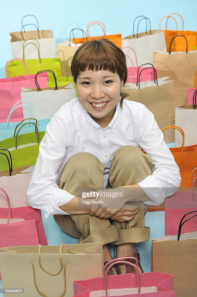 A lot of shopping bags and the woman who sit down : Stock Photo