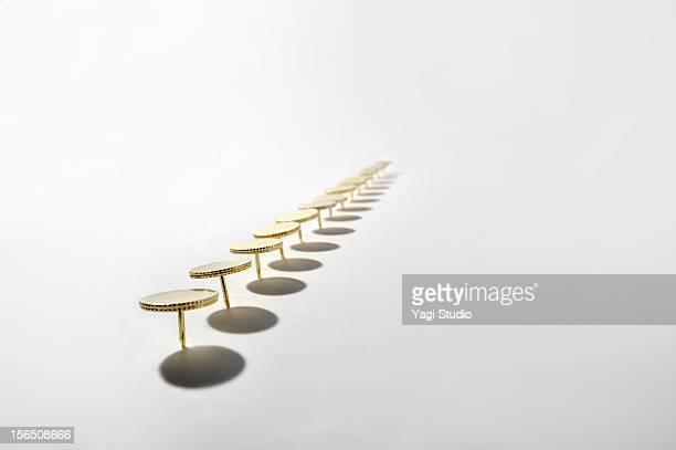 A lot of thumbtacks form a line