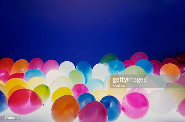 Viele bunte Ballons auf blauem Hintergrund, leichte von unten