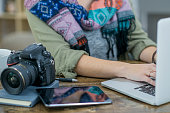 A female Caucasian photographer is indoors in a design studio. She is wearing casual clothing and a stylish shawl. She is working on her laptop computer. A camera and tablet computer are on her desk.