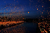A large collection of flying chinese lanterns next to the River