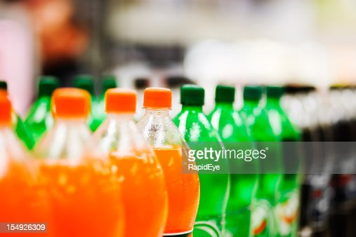 Lots of soda bottles in various flavours all lined up