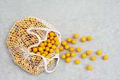 Lots of yellow plums in a cotton mesh shopping bag, on concrete background.