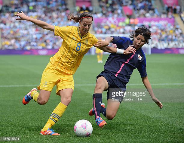 Lotta Schelin of Sweden is challenged by Saki Kumagai of Japan during the Women's Football first round Group F Match of the London 2012 Olympic Games...