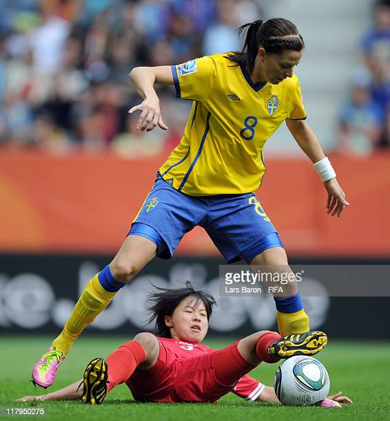 Lotta Schelin of Sweden is challenged by Song Jong Sun of Korea DPR during the FIFA Women's World Cup Group C match between Korea DPR and Sweden at...