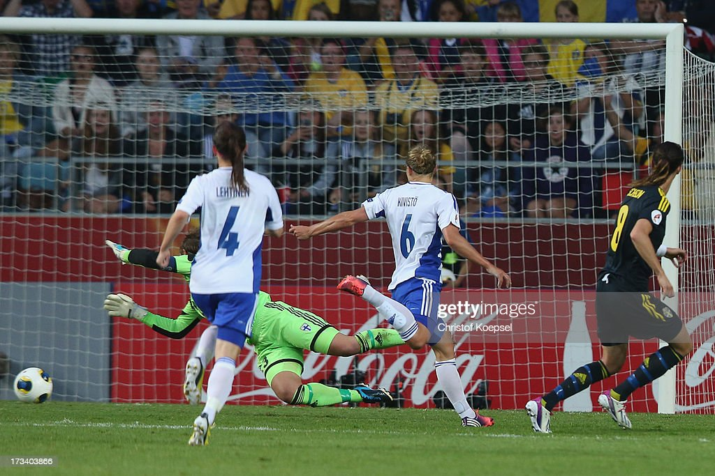 <a gi-track='captionPersonalityLinkClicked' href=/galleries/search?phrase=Lotta+Schelin&family=editorial&specificpeople=742197 ng-click='$event.stopPropagation()'>Lotta Schelin</a> of Sweden (R) scores the forth goal against Susanna Lehtinen (L9, Tinja-Riikka Korpela (2nd L) and Laura Kivistoe (3rd L) of Finland during the UEFA Women's EURO 2013 Group A match between Finland and Sweden at Gamla Ullevi Stadium on July 13, 2013 in Gothenburg, Sweden.