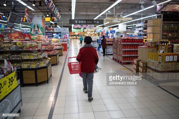 A Lotte Mart staff stands in an almost empty Lotte Mart in Shanghai on March 13 2017 The store remained open but dozens of other Lotte stores in...