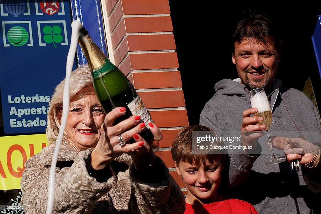 Lottery administration shop owner Maria Luisa (L) celebrates with Juan Luis Moreno (R) whose mother won a top prize ticket number in Spain's Christmas lottery, 'El Gordo' (Fat One) on December 22, 2013 in Leganes, near Madrid, Spain. This year's winning number is 62246, with a total of 4 million euros for the top prize to be shared between ten ticket holders. The total prize fund is worth 2.5bn.