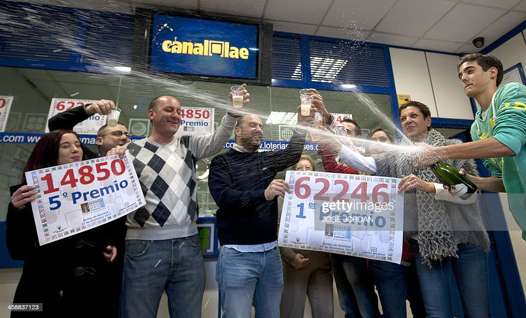 Lottery Administration shop owners celebrate having sold the first prize (C) in Spain's Christmas lottery named 'El Gordo' (Fat One) in Manises, near Valencia on December 22, 2013 . This year's winning number is 62246 presenting winnings of 4 million euros.