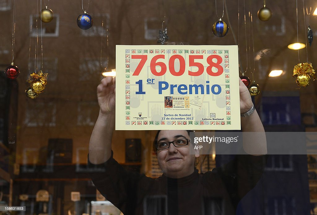 A lottery seller who sold the winning ticket of Spain's Christmas lottery hangs a placard reading the winning number 76058 on her shop windowcase in Madrid, on December 22, 2012. The world's richest lottery showered prizes of up to 2.5 billion euros ($3.3 billion) on crisis-hit Spaniards in an annual draw of the 'El Gordo' or 'The Fat One'. The jackpot went to number 76058, which is split into a total of 1,800 'decimo' tickets each paying out 400,000 euros.