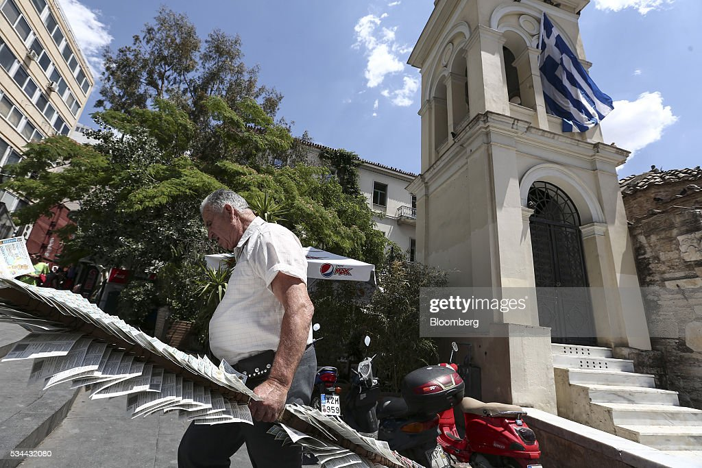 A lottery ticket seller carries his ticket board past a church flying Greek national flag in Athens, Greece, on Thursday, May 26, 2016. Greece may have passed a milestone and its bond market has been lucrative for some investors, but the road to recovery doesn't look much shorter. Photographer: Yorgos Karahalis/Bloomberg via Getty Images