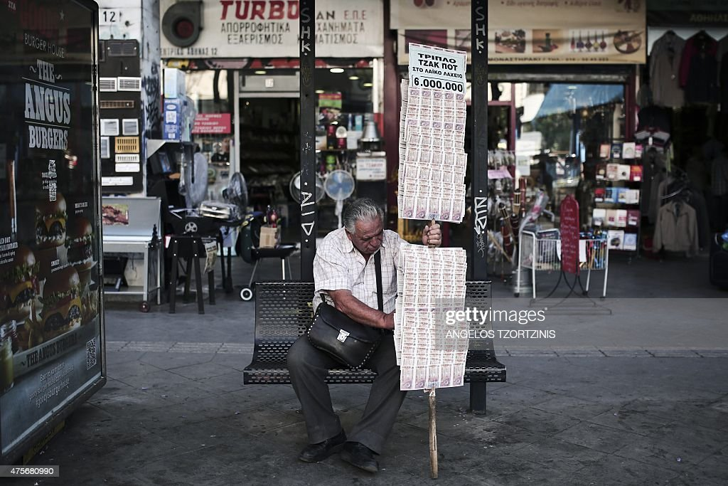 A lottery ticket seller rests at a busstop in Athens on June 3 2015 as Greek Prime Minister will meet European Commission President today for...