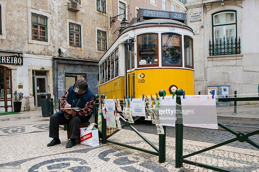 A lottery ticket vendor sits and waits for customers near a tram stop in Lisbon, Portugal, on Monday, April 8, 2013. Portugal will carry out more spending cuts this year after the Constitutional Court blocked a plan to suspend a monthly salary payment to state workers and pensioners. Photographer: Mario Proenca/Bloomberg via Getty Images