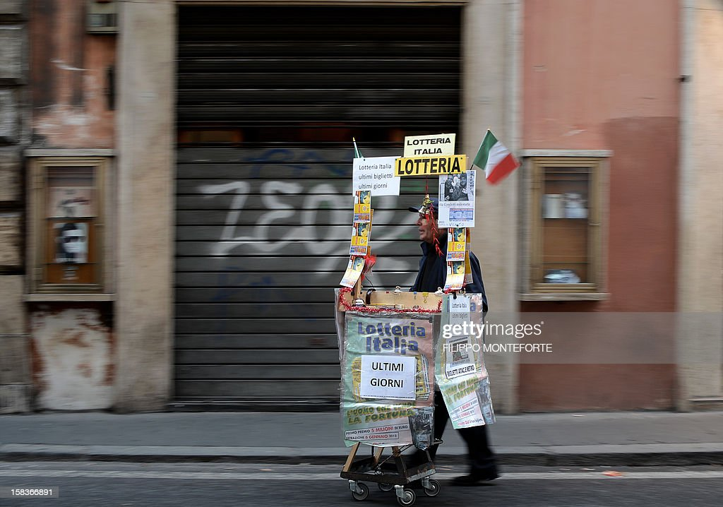A lottery tickets streetseller walks in front of a closed shop in downtown Rome on December 14, 2012. Italy's public debt crossed the two-trillion-euro mark for the first time in October when it reached a record high of 2.014 trillion, the Bank of Italy said on Friday. AFP PHOTO/ Filippo MONTEFORTE