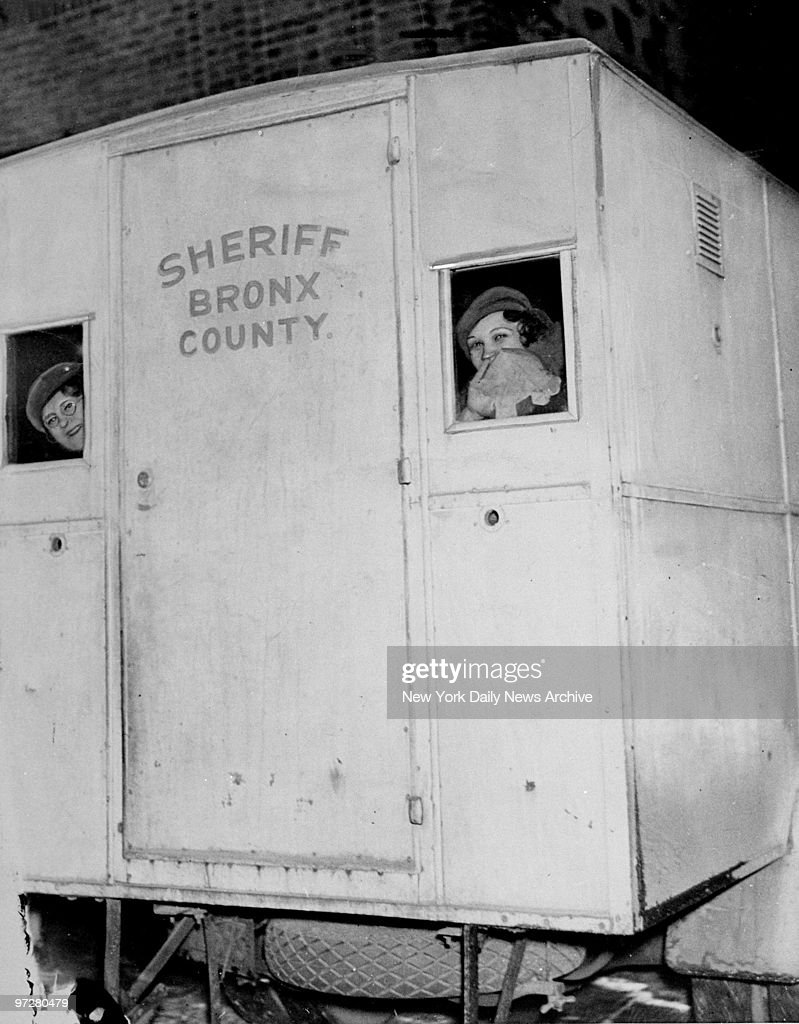 Lottie Coll (right), widow of killer Vincent (Mad Dog) Coll, looks out of the patrol wagon on her way to jail after the opening of her murder trial.