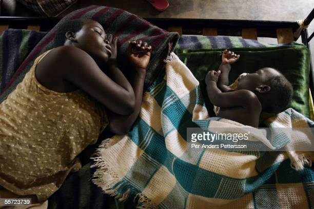 Lotu Sarah age 17 sleeps with her baby Omong Solomon at a center for rehabilitation of child mothers run by Worldvision an NGO on Aug 4 2005 in Gulu...