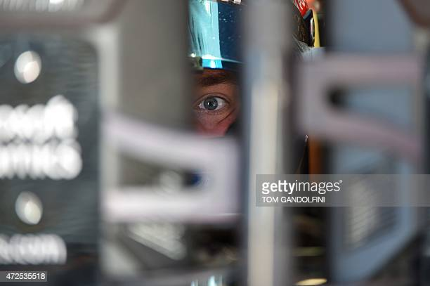 Lotus F1 Team's French driver Romain Grosjean looks through a control screen in the pits during the first practice session at the Circuit de...