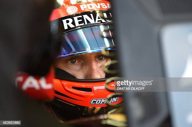 Lotus' French driver Romain Grosjean looks at a control screen the pits in the pits during the first practice session at the Hungaroring circuit in...
