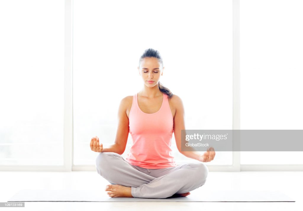Lotus position - Young casual woman practicing yoga : Stock Photo