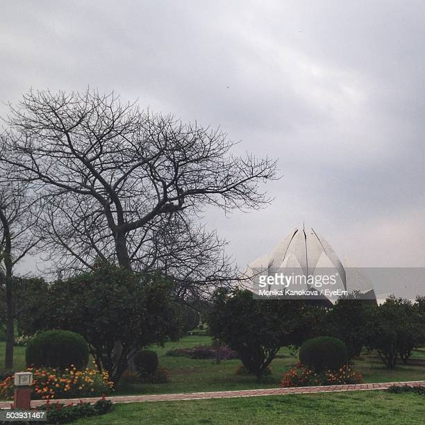 Lotus temple surrounded by formal garden against cloudy sky