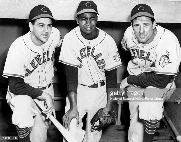 Lou Boudreau Larry Doby and Manager Hank Greenberg of the Cleveland Indians pose in the dugout during a season game Lou Boudreau played for the...