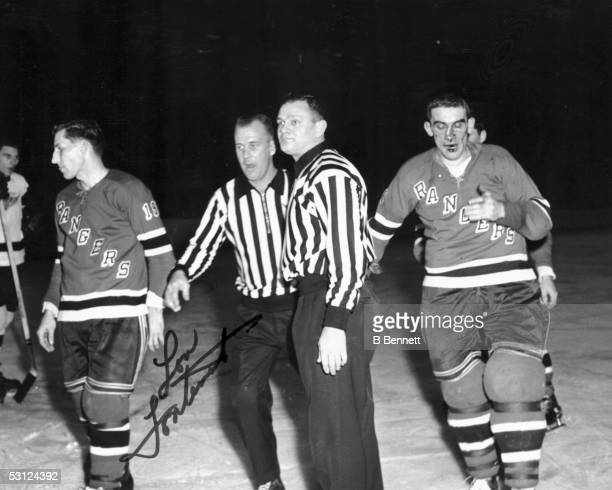 Lou Fontinato of the New York Rangers is bloodied after a fight with Gordie Howe of the Detroit Red Wings as Lou's teammate Larry Popein looks on...