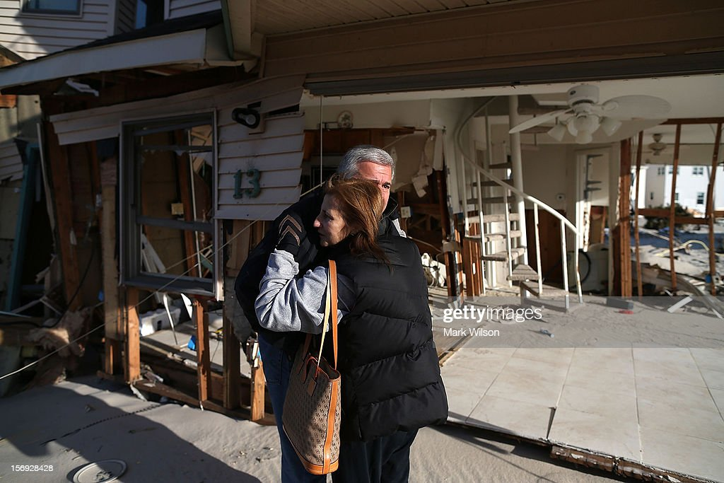 Lou Friedella gets a hug from his wife Susan in front of their beach house that was damaged by Superstorm Sandy on November 25, 2012 in Ortley Beach, New Jersey. The Friedella's owned their beach house for 31 years before Superstorm Sandy moved it off its foundation and partially demolished it.