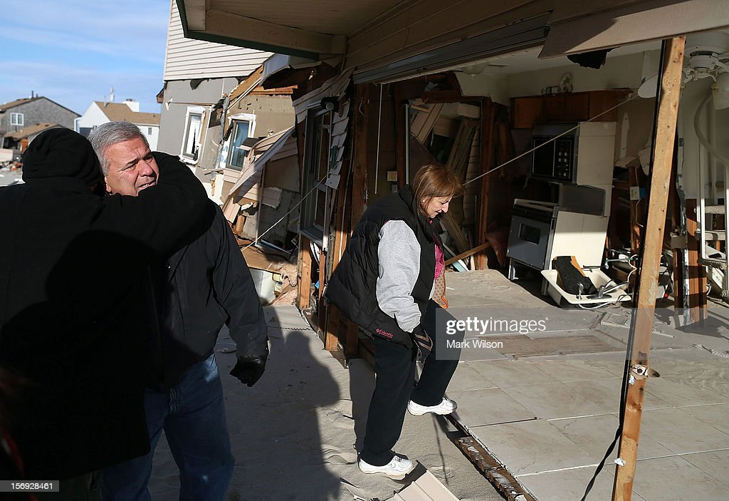 Lou Friedella (2nd-L), is in tears as he gets a hug from his son Christopher (L), flanked by his wife Susan, front of their beach house that was damaged by Superstorm Sandy on November 25, 2012 in Ortley Beach, New Jersey. The Friedella's owned their beach house for 31 years before Superstorm Sandy moved it off its foundation and partially demolished it.