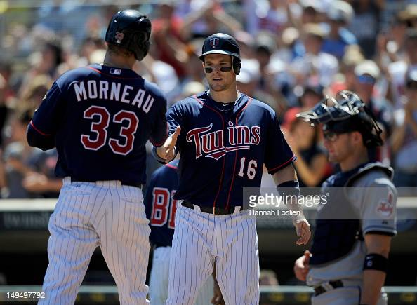 Lou Marson of the Cleveland Indians looks on as Josh Willingham of the Minnesota Twins congratulates Justin Morneau on a two run home run during the...