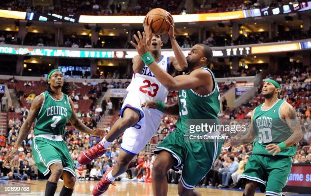 Lou Williams of the Philadelphia 76ers drives for a shot attempt against Marquis Daniels Shelden Williams and Eddie House of the Boston Celtics at...