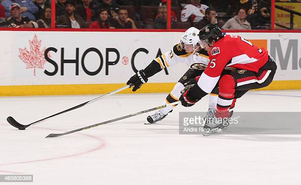 Loui Eriksson of the Boston Bruins reaches to deke the puck back against Cody Ceci of the Ottawa Senators at Canadian Tire Centre on March 10 2015 in...
