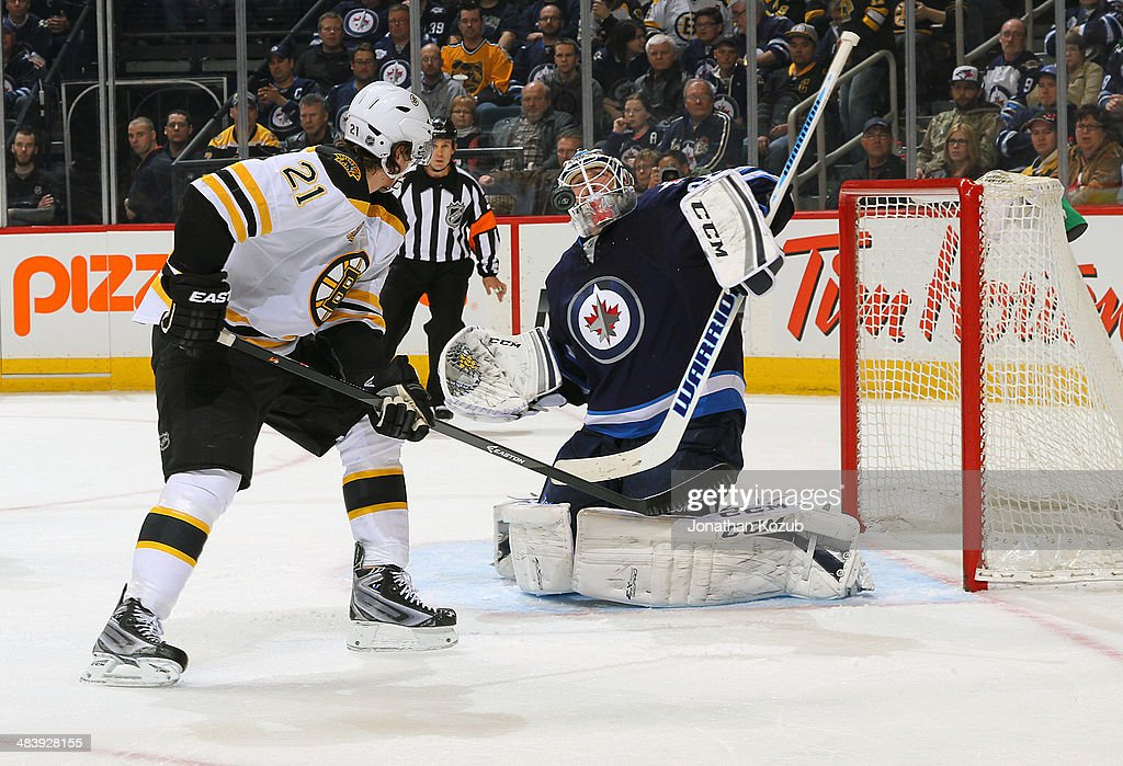 Loui Eriksson #21 of the Boston Bruins watches as the puck deflects high on goaltender Michael Hutchinson #34 of the Winnipeg Jets during second period action at the MTS Centre on April 10, 2014 in Winnipeg, Manitoba, Canada.