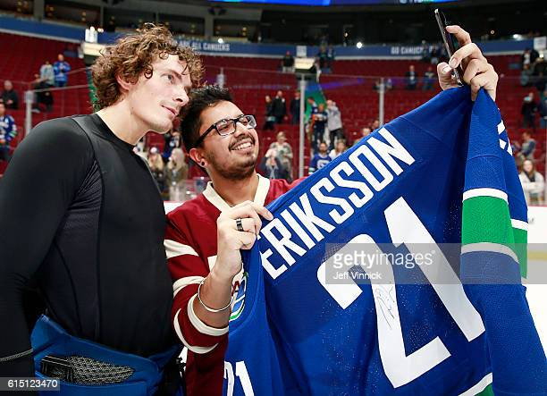Loui Eriksson of the Vancouver Canucks poses for a selfie with the fan who won his game jersey on shirtoffyourback night after the Canucks beat the...